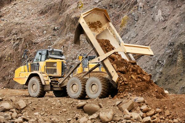 Caterpillar articulated dump truck emptying rocky soil
