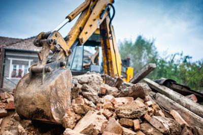 Excavator bucket removing demolition rubble