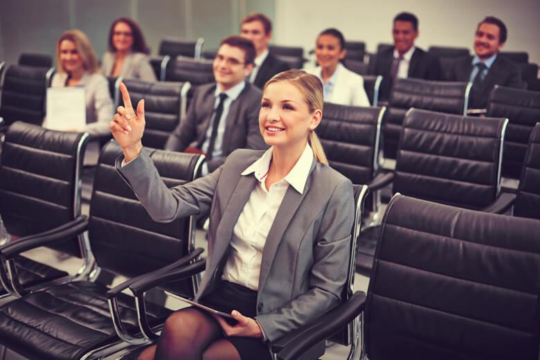 mujer profesional levantando su mano para preguntar algo del presentador