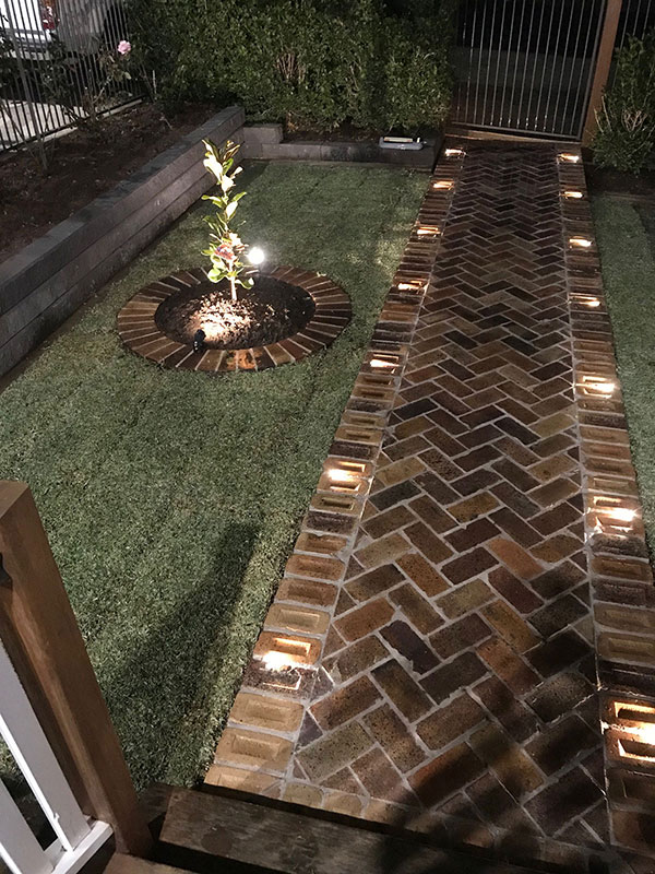 A Brick foot path with precise landscaping.