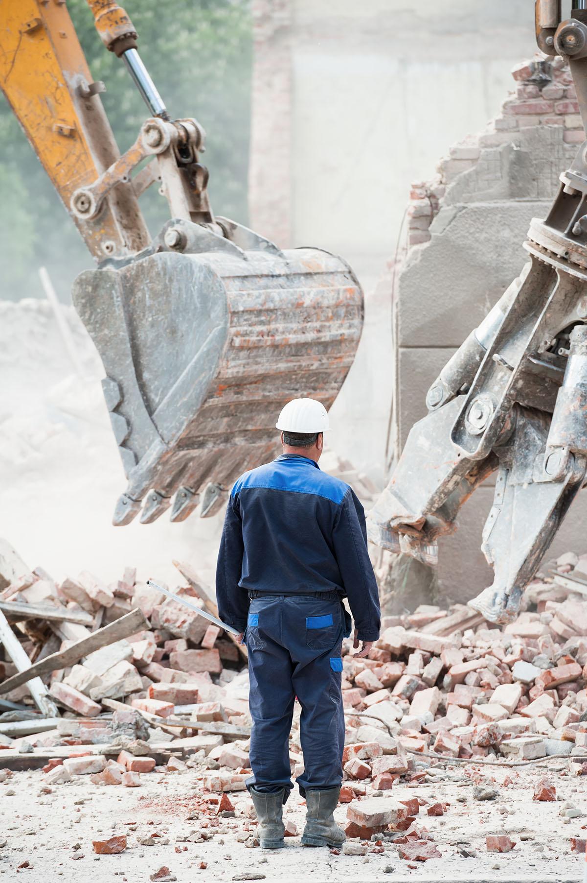 Excavator, man at building demolition site