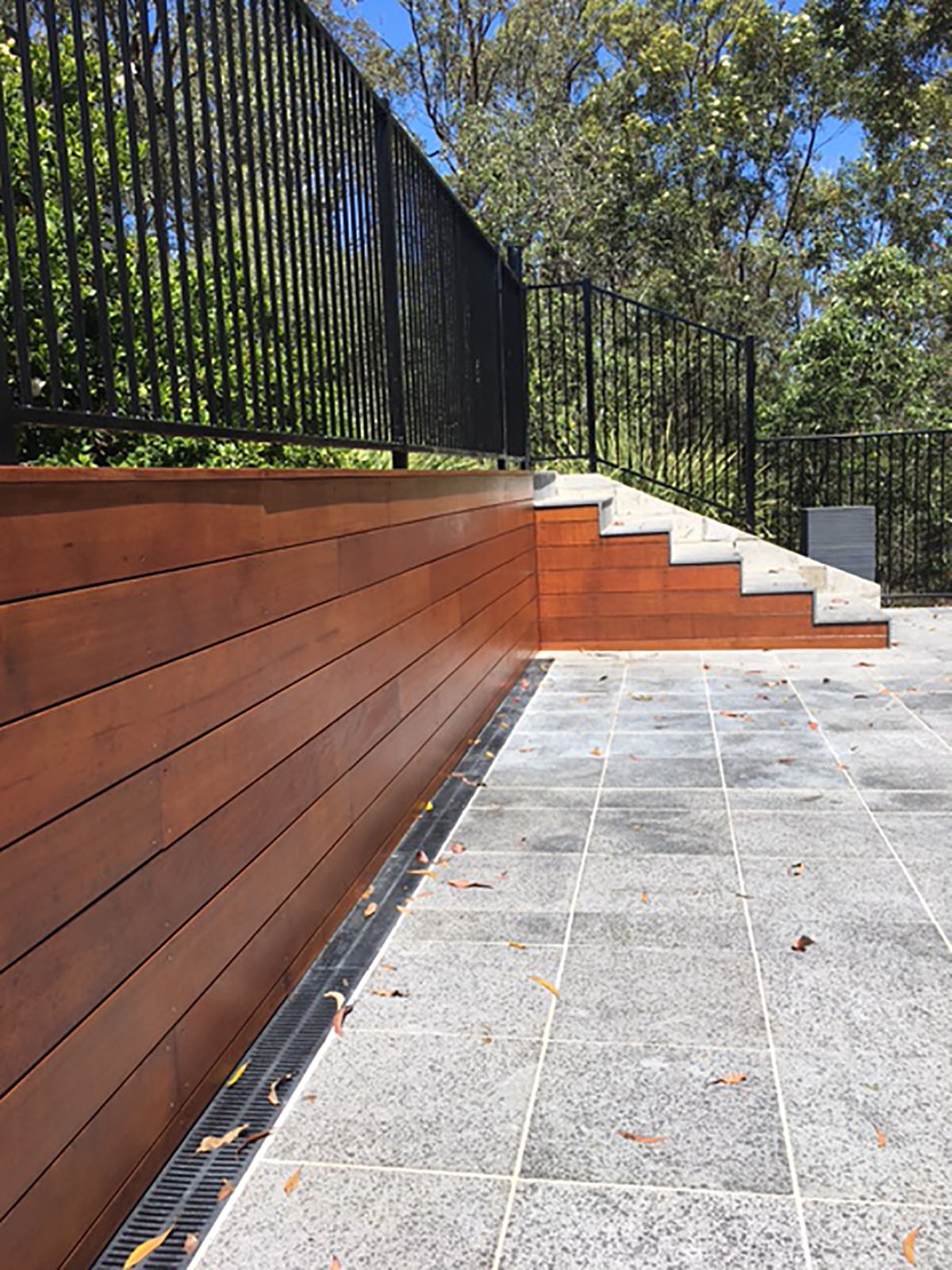 Hoys Merbau faced retaining wall with Granite paving and flat top pool fencing