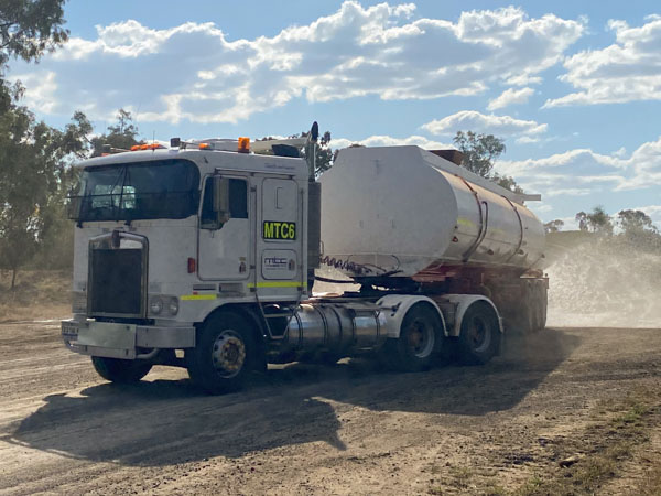 Kenworth K104 towing a water tank