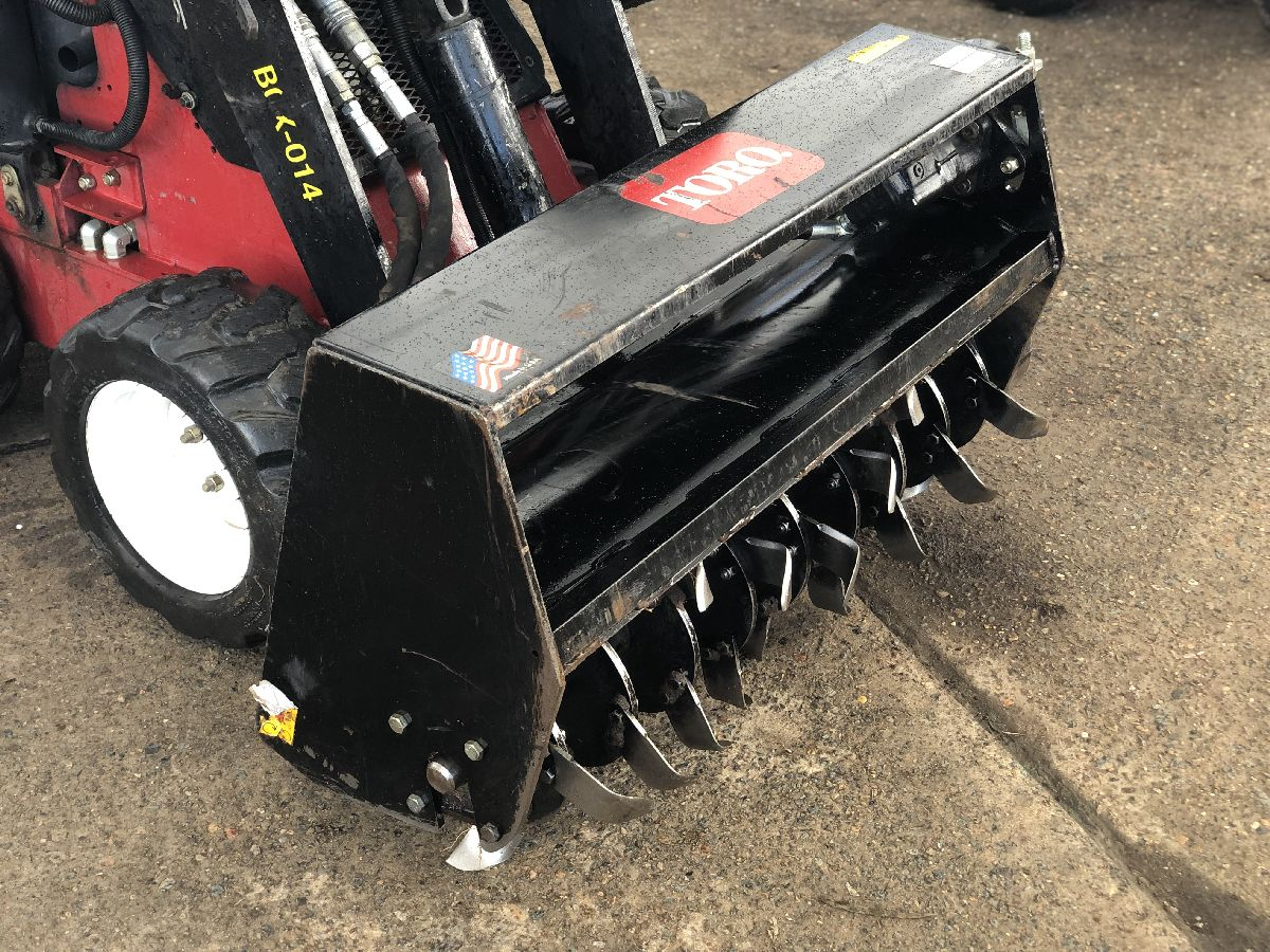 At Online Hire we hire mini skid steer loaders; this image shows a rotary hoe attachment from the left hand side