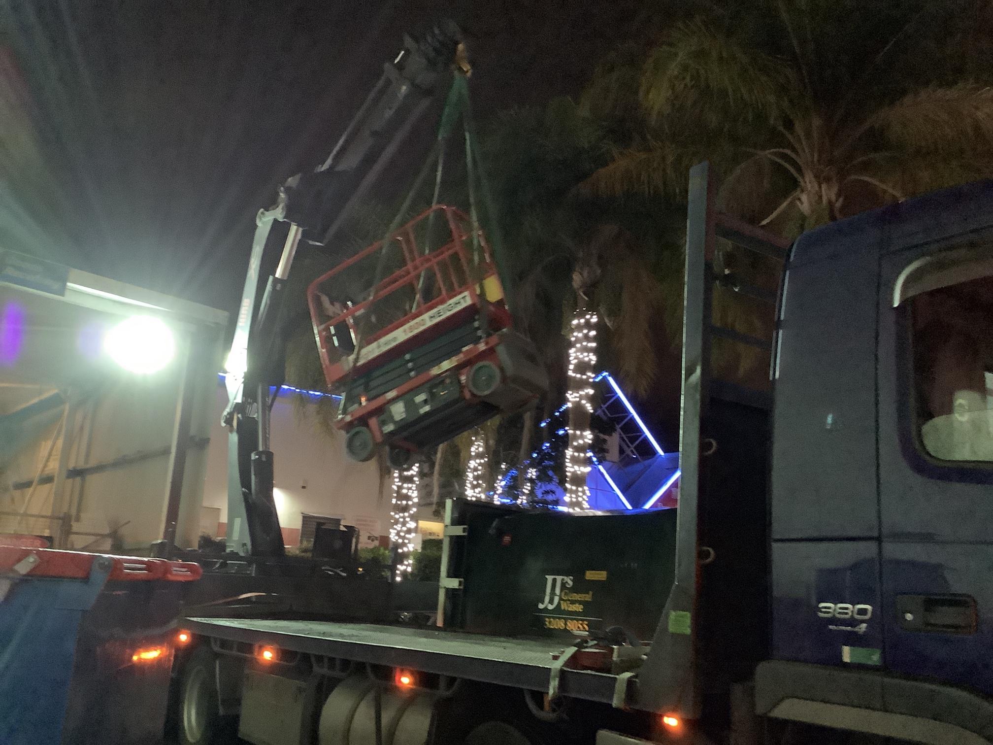 hired crane truck lifts fallen scissor