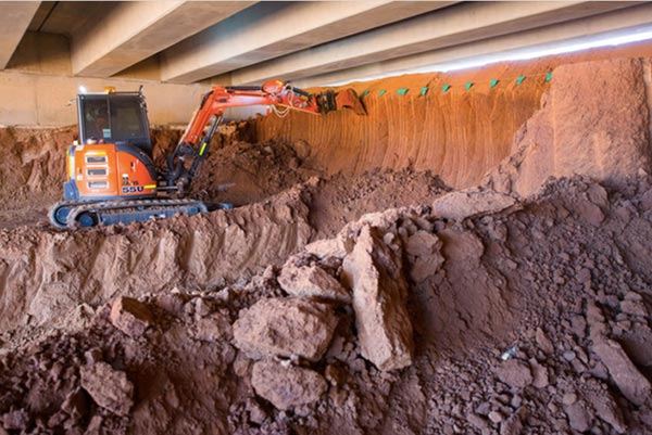 Mini excavator under bridge