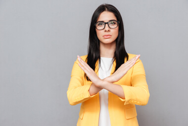 una mujer profesional haciendo un x con sus brazos