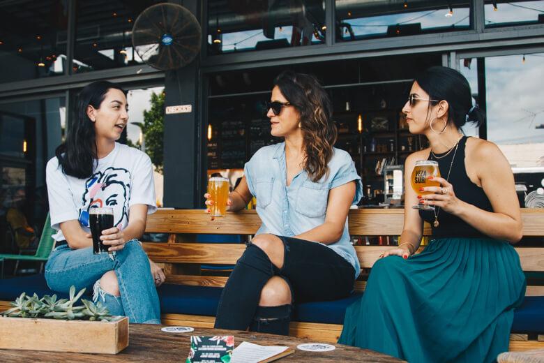 tres mujeres tomando cervezas en una mesa a fuera