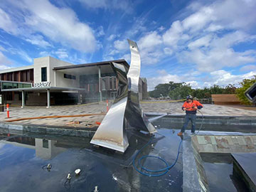 Ezali Hydro Excavation & Communications Water Jet cleaning hosing statue at library in Toowoomba