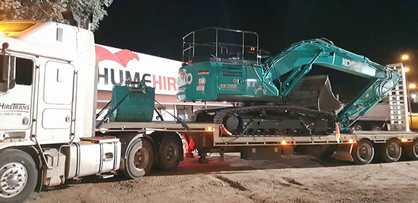 Hume Hire excavator transport services at night Lavington