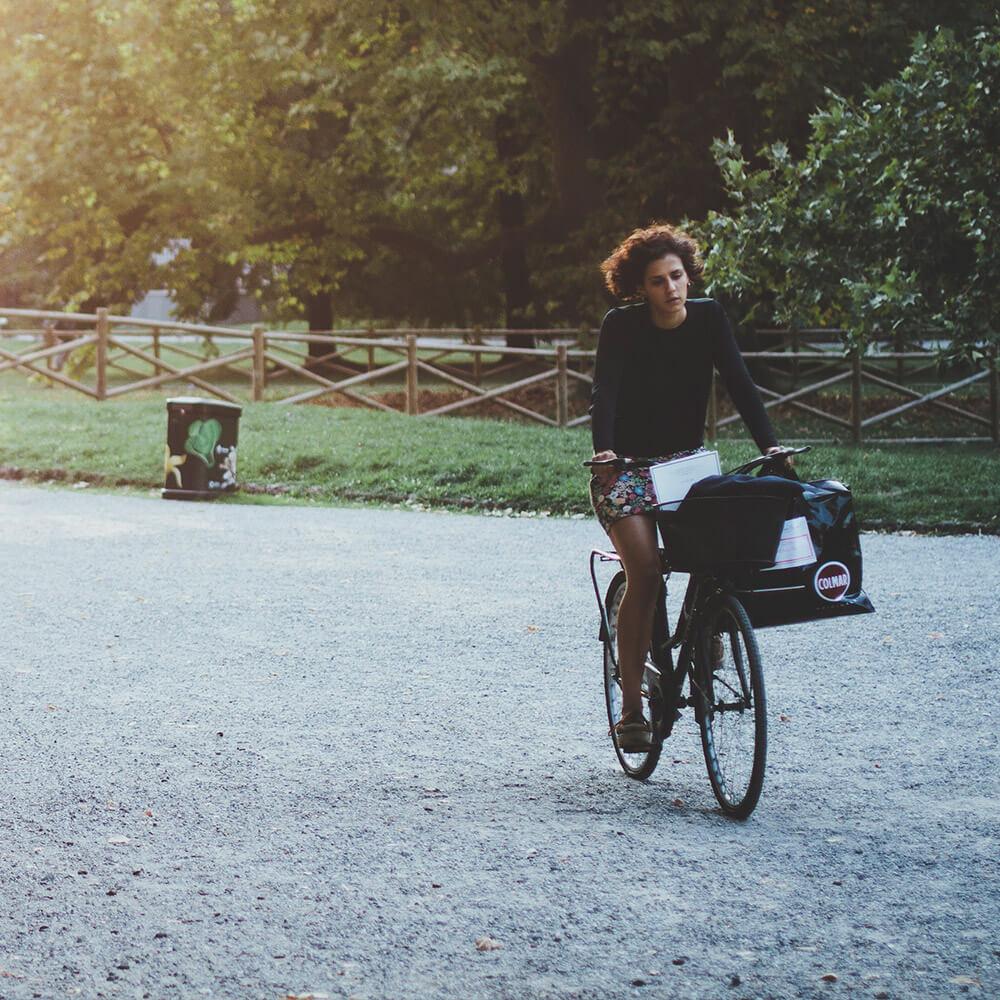 An outside portrait photograph of a lady on a bike