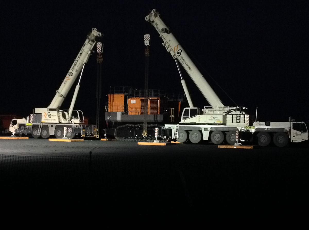 two franna cranes lifting large excavator