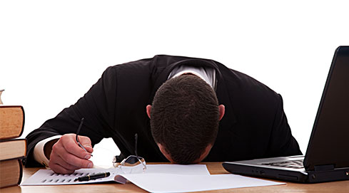 Man despairing with head down on desk